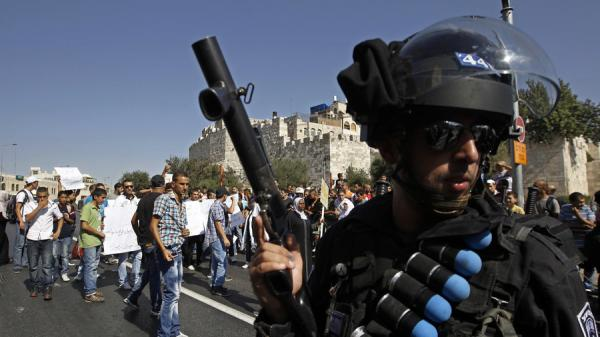 Israeli policemen wearing a belt with rubber bullets stands near Palestinian protesters, 2012