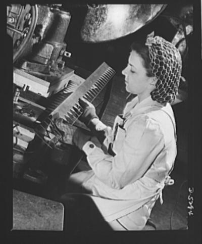 A young woman worker ‎operates a heavy punch-press in a large Western aircraft plant, USA 1942, fotografia di David ‎Bransby, dal database della Library of Congress.‎