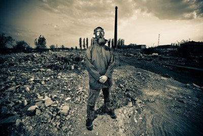 9642119-bizarre-portrait-of-man-in-gas-mask-on-smoky-industrial-background-with-pipes-after-nuclear-disaster