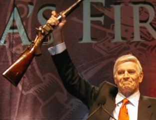 Charlton Heston sventola un fucile durante una riunione della National Rifle Association