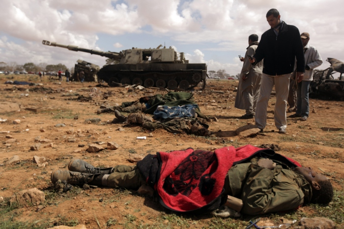 Curious Libyan onlookers take pictures of dead African teenagers, members of Muammar Qaddafi's forces hit by airstrikes by French warplanes in al-Wayfiyah west of Benghazi, on March 20 in al-Wayfiyah. (Patrick Baz/AFP/Getty Images)