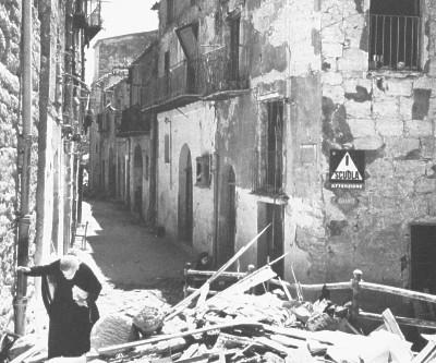 Sicilia, 1943. Un'anziana donna tra le rovine del suo paese. Sicily, 1943. And old woman walking in the ruins of her village.