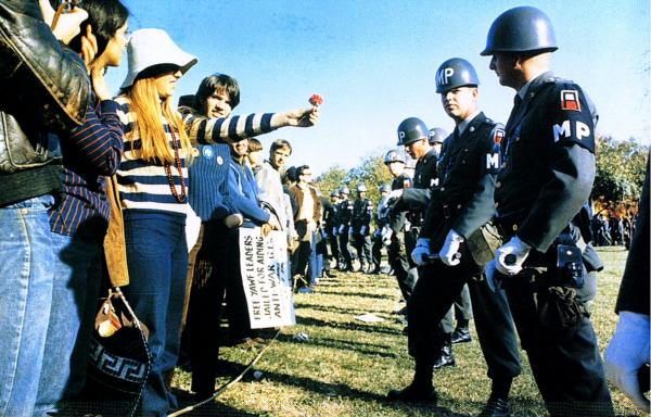 Anti-Vietnam demonstrator offers a flower to a miltary police, Arlington, Virginia, October 21, 1967
